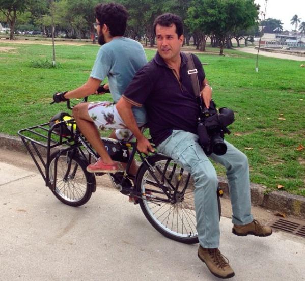 O jornalista André Trigueiro pega uma carona em bicicleta/